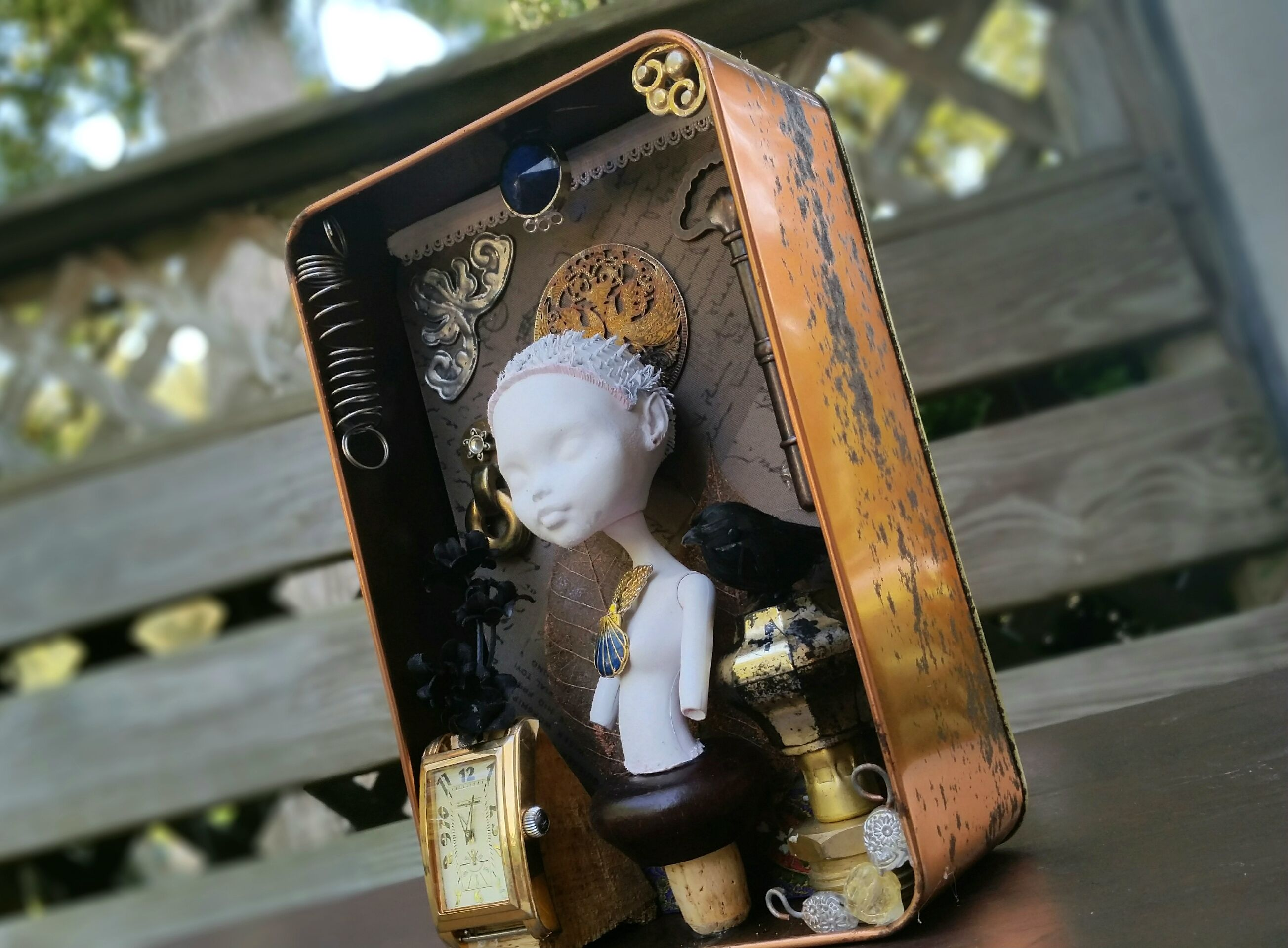 finished assemblage piece, a bust of a doll with a semi-steampunk aesthetic