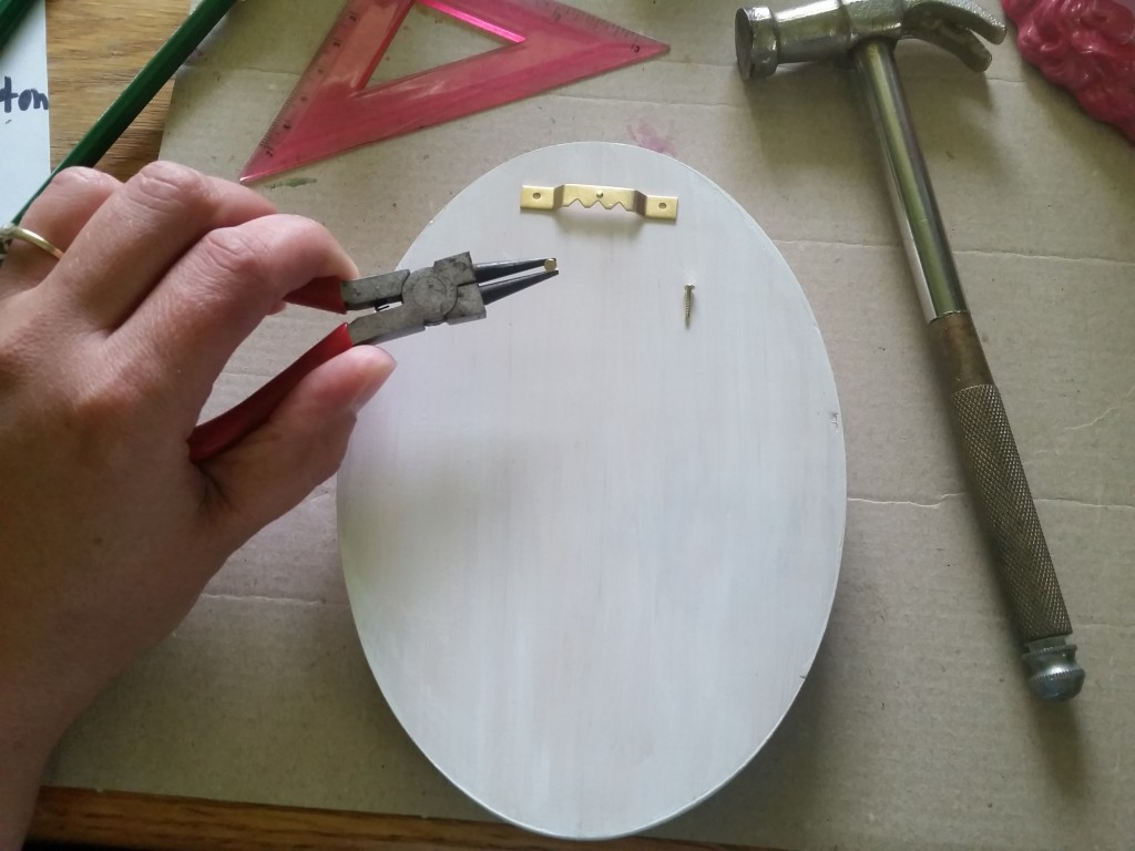 attaching a saw-tooth hanger to the back of a wooden plaque