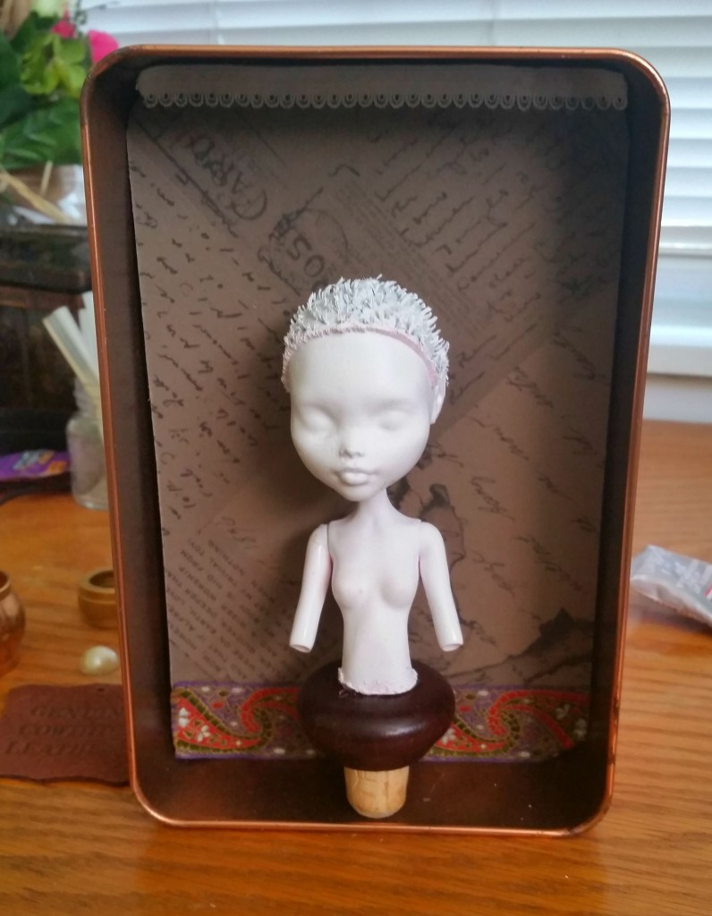 half-finished assemblage with a white spray-painted doll bust